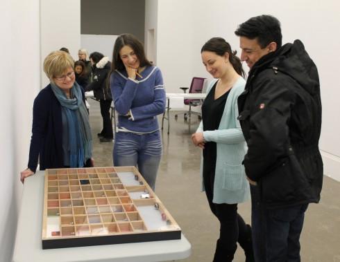 VAM volunteers and artist Antonio Caballero examine his work at the AGM prior to installation